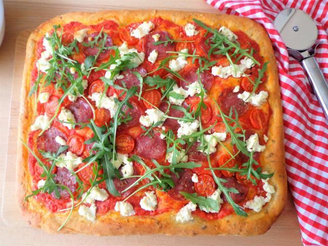 Pizza na grubym cieście z salami, pomidorkami, ricottą i rukolą